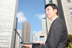 オフィス街でパソコンをするビジネスマンの写真素材 [FYI00032830]