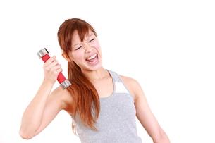 厳しいダンベル体操を頑張る女性の写真素材 [FYI00035760]
