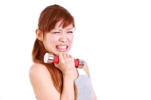 厳しいダンベル体操を頑張る女性の写真素材 [FYI00035764]