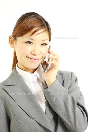 スマートフォンで電話をするビジネスウーマンの写真素材 [FYI00035981]