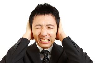 騒音に耐えかねているビジネスマンの写真素材 [FYI00036131]