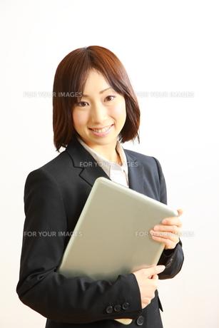 パソコンを抱えるビジネスウーマンの写真素材 [FYI00036241]