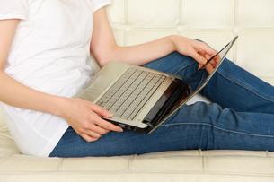 自宅のソファーでパソコンを使う女性の写真素材 [FYI00036288]