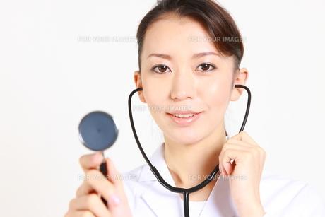 聴診器で診察する白衣姿の女性医師の写真素材 [FYI00036354]