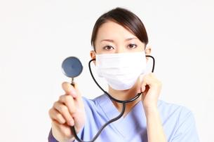 聴診器で診察する手術衣姿の女性医師の写真素材 [FYI00036382]