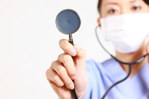 聴診器で診察する手術衣姿の女性医師の写真素材 [FYI00036388]