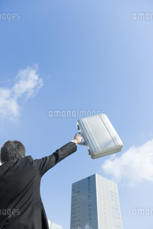 アタッシュケースを高く上げるビジネスマンの写真素材 [FYI00040060]