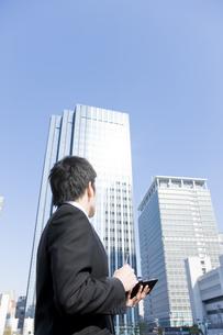 屋外で手帳にメモするビジネスマンの写真素材 [FYI00040062]