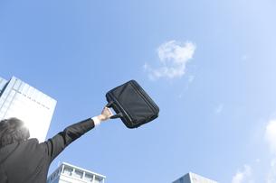 ビジネスバッグを高く上げるビジネスマンの写真素材 [FYI00040073]