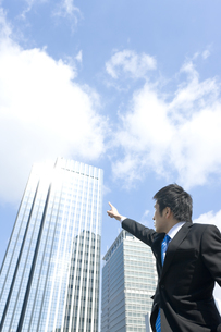 高層ビルを指差すビジネスマンの写真素材 [FYI00040080]