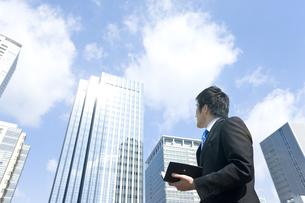 高層ビルを見上げるビジネスマンの写真素材 [FYI00040081]
