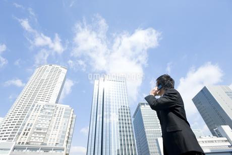 屋外で携帯電話をかけるビジネスマンの写真素材 [FYI00040083]