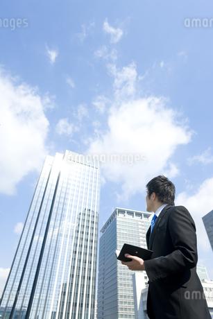 高層ビルを見上げるビジネスマンの写真素材 [FYI00040085]