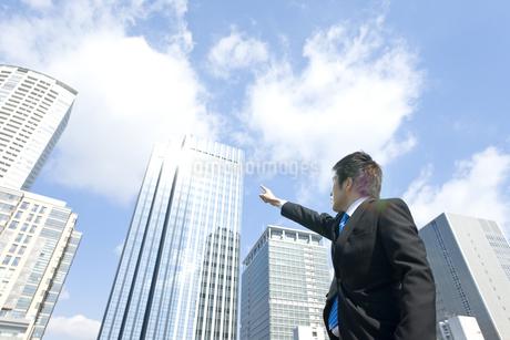 高層ビルを指差すビジネスマンの写真素材 [FYI00040093]