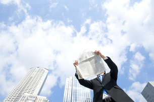 屋外で新聞を読むビジネスマンの写真素材 [FYI00040102]