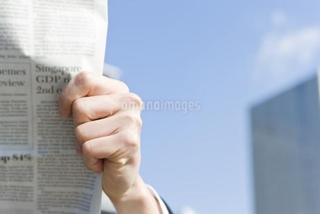 屋外で新聞を読むビジネスマンの写真素材 [FYI00040109]