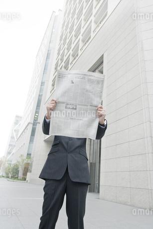 屋外で新聞を読むビジネスマンの写真素材 [FYI00040139]