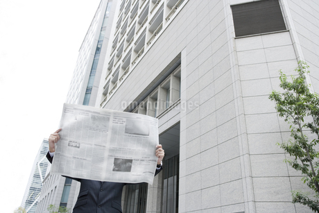 屋外で新聞を読むビジネスマンの写真素材 [FYI00040140]