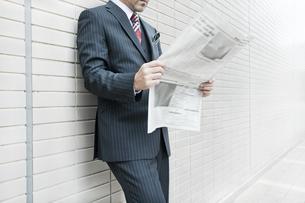 屋外で新聞を読むビジネスマンの写真素材 [FYI00040144]