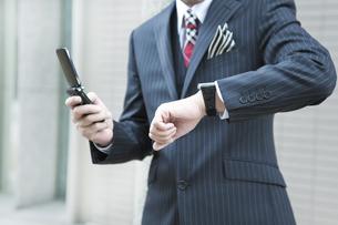 屋外で携帯電話をかけるビジネスマンの写真素材 [FYI00040148]
