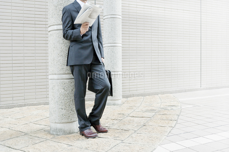 屋外で新聞を読むビジネスマンの写真素材 [FYI00040156]