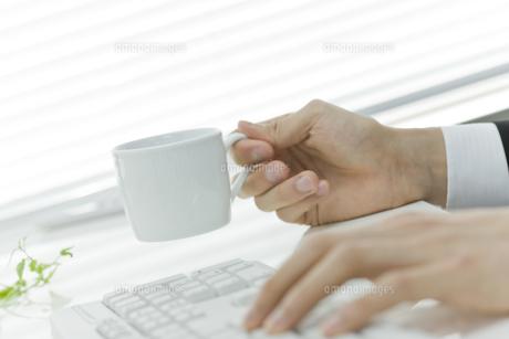 カップを持ちながらキーボードを操作する男性の写真素材 [FYI00040157]