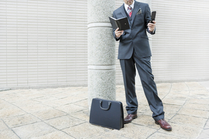 屋外で携帯電話をかけるビジネスマンの写真素材 [FYI00040171]