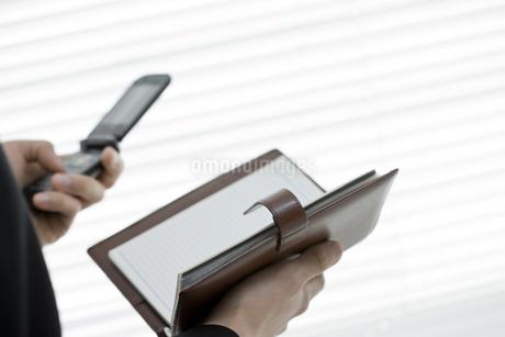 携帯電話と手帳を持つ男性の手元の写真素材 [FYI00040172]