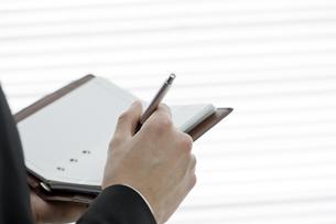 手帳に記入する男性の手元の写真素材 [FYI00040183]