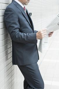 屋外で新聞を読むビジネスマンの写真素材 [FYI00040196]