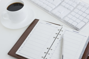 デスクの上の手帳とコーヒーカップの写真素材 [FYI00040269]