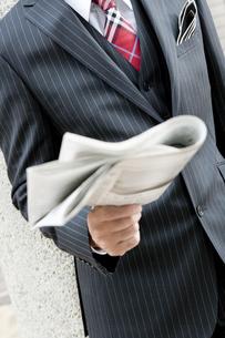 屋外で新聞を読むビジネスマンの写真素材 [FYI00040409]