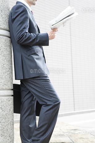屋外で新聞を読むビジネスマンの写真素材 [FYI00040410]