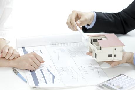 住宅模型で説明する営業マンの写真素材 [FYI00040664]