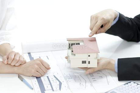 住宅模型で説明する営業マンの写真素材 [FYI00040703]