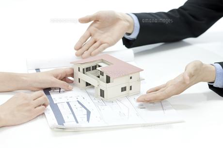 住宅模型を渡す営業マンの写真素材 [FYI00040704]