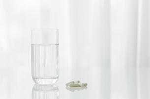 テーブルに置かれた薬とコップの写真素材 [FYI00040826]