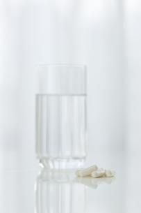 テーブルに置かれた薬とコップの写真素材 [FYI00040827]