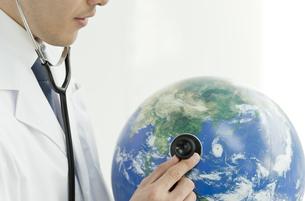 地球儀に聴診器をあてる医師の写真素材 [FYI00040831]