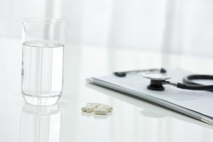 テーブルに置かれた薬とコップの写真素材 [FYI00040839]