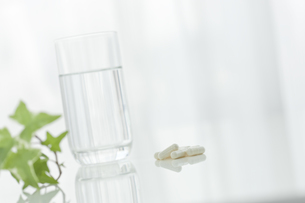 テーブルに置かれた薬とコップの写真素材 [FYI00040884]