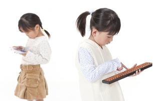 そろばんと電卓を持つ女の子の写真素材 [FYI00040965]
