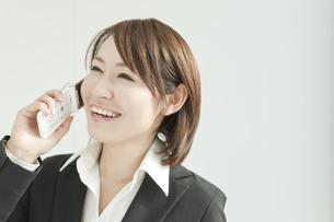 笑いながら電話をかけるビジネスウーマンの写真素材 [FYI00041209]
