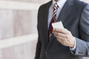 スマートフォンを操作するビジネスマンの写真素材 [FYI00041808]
