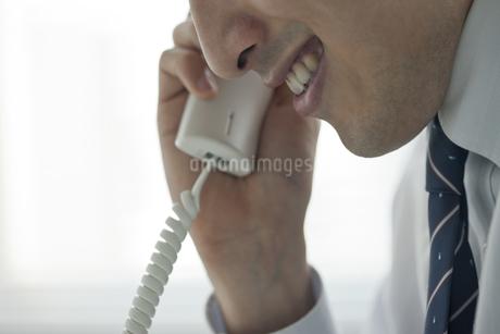 不気味な笑みを浮かべ電話をする男性の写真素材 [FYI00041897]
