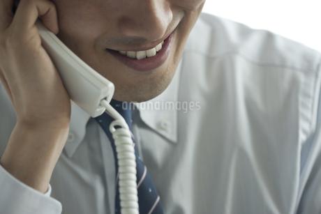 不気味な笑みを浮かべ電話をする男性の写真素材 [FYI00041911]
