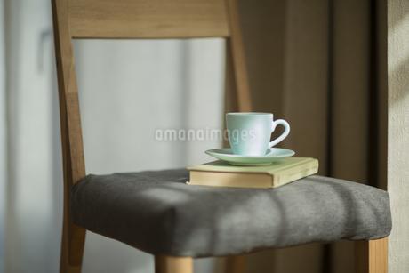 椅子の上にあるコーヒーカップと本の写真素材 [FYI00042550]