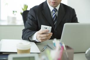 スマートフォンを操作するビジネスマンの写真素材 [FYI00042803]