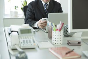 スマートフォンを操作するビジネスマンの写真素材 [FYI00042809]