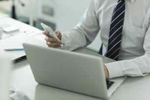 スマートフォンを操作するビジネスマンの写真素材 [FYI00042832]